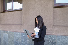 Beautiful young girl entrepreneur holds laptop and works, solves Royalty Free Stock Photos