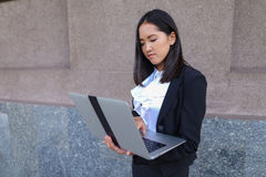 Beautiful young girl entrepreneur holds laptop and works, solves Stock Image