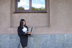 Beautiful young girl entrepreneur holds laptop and works, solves Royalty Free Stock Images