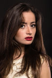 Beautiful young girl in extraordinary form on a dark background Royalty Free Stock Photography