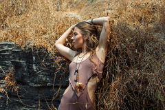 Beautiful young girl in fancy clothes among dry grass and the rock. Stock Photos