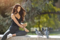 Beautiful young girl feeding pigeons. Happy travel woman. Travel tourist girl on vacation resting happy outdoors. Attractive young romantic woman sitting stock images