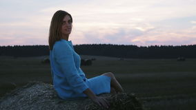 Beautiful young girl in the field. Woman looks into the distance and relaxes in nature. Over sunset sky. Side view stock video