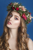 Beautiful young girl with a floral ornament in her hair on a blue background. Woman in wreath of flowers.Beauty Face. Fashion phot Stock Photos