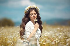 Beautiful young girl with flower enjoying in chamomile field. Carefree happy brunette woman with chaplet on healthy wavy hair stock image