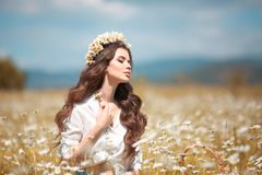 Beautiful young girl with flower enjoying in chamomile field. Carefree happy brunette woman with chaplet on healthy wavy hair royalty free stock photography