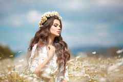 Beautiful young girl with flower enjoying in chamomile field. Carefree happy brunette woman with chaplet on healthy wavy hair. Having fun outdoor in nature stock photography