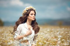 Beautiful young girl with flower enjoying in chamomile field. Carefree happy brunette woman with chaplet on healthy wavy hair. Having fun outdoor in nature stock photo