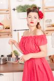 Beautiful young girl with flower in her hair posing in red pin up polka dot dress at home in the kitchen. Pretty pin up woman wearing red polka dot dress and stock photography