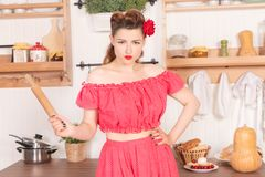 Beautiful young girl with flower in her hair posing in red pin up polka dot dress at home in the kitchen. Pretty pin up woman wearing red polka dot dress and stock image