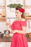 Beautiful young girl with flower in her hair posing in red pin up polka dot dress at home in the kitchen. Pretty pin up woman wearing red polka dot dress and royalty free stock images