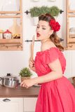 Beautiful young girl with flower in her hair posing in red pin up polka dot dress at home in the kitchen. Pretty pin up woman wearing red polka dot dress and stock images
