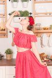 Beautiful young girl with flower in her hair posing in red pin up polka dot dress at home in the kitchen. Pretty pin up woman wearing red polka dot dress and royalty free stock image