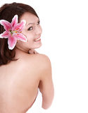 Beautiful young girl with flower in spa. Stock Photo