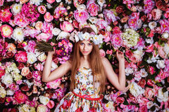 A beautiful young girl with flowers bouquet near a floral wall. Royalty Free Stock Photos