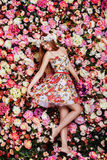 A beautiful young girl with flowers bouquet near a floral wall. Royalty Free Stock Image