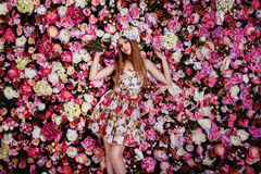 A beautiful young girl with flowers bouquet near a floral wall. Royalty Free Stock Photo