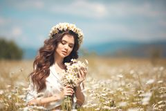 Beautiful young girl with flowers enjoying in chamomile field. Carefree happy brunette woman with chaplet on healthy wavy hair. Having fun outdoor in nature royalty free stock photography