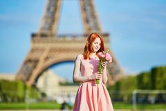 Girl with traditional French flowers in front of the Eiffel tower. Beautiful young girl with flowers in front of the Eiffel tower Stock Photo