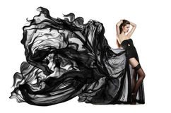 Beautiful young girl in flying black dress. Flowing fabric Stock Images