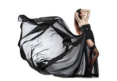Beautiful young girl in flying black dress. Flowing fabric stock image