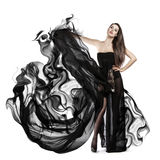 Beautiful young girl in flying black dress. Flowing fabric Stock Photography