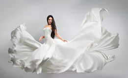 Beautiful young girl in flying white dress. Flowing fabric. Light white cloth flying Stock Images
