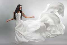 Beautiful young girl in flying white dress. Flowing fabric. Light white cloth flying. In the wind Stock Photo