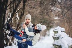 Beautiful young girl fun piggybacking on boyfriend in winter in the park. stock photo