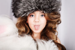 Beautiful young girl in fur cap puts out the tongue Stock Photos