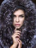 Beautiful young girl in fur clothes. Studio shot stock photos