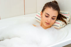 Beautiful young girl gently rests in the bath with foam drooping eyes Stock Photography
