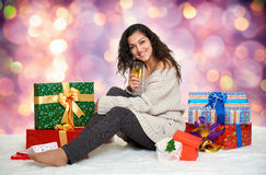 Beautiful young girl with a glass of champagne and gift boxes Royalty Free Stock Images