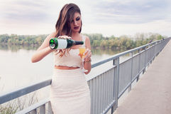 Beautiful young girl  with a glass of champagne . Beautiful  girl in a white dress with a glass of champagne on the bridge Stock Image