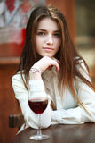 Beautiful young girl with glass of red wine, alone in a restaura Stock Photo