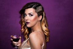 Beautiful girl with a glass of wine in hand with curly golden hairstyle posing in front of purple wall stock photography