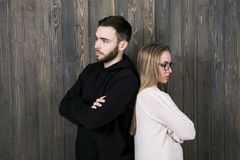 A beautiful young girl with glasses and a young man in black clo. A beautiful young girl with glasses and a young men in black clothes with a hood quarreled and Royalty Free Stock Photography