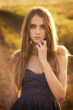 Beautiful young girl goes on a flower meadow at su Royalty Free Stock Photos
