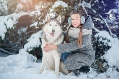 Beautiful young girl in a gray coat in winter forest with Siberian Husky. Symbol of new year 2018. Stock Photos