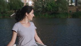 Beautiful young girl is sitting in a boat stock footage