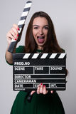 Beautiful young girl in green dress is holding a clapperboard Stock Photos