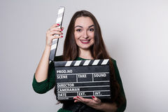 Beautiful young girl in green dress is holding a clapperboard Stock Photography