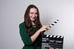 Beautiful young girl in green dress is holding a clapperboard Royalty Free Stock Photo
