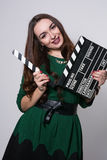 Beautiful young girl in green dress is holding a clapperboard Stock Image