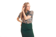 Beautiful young girl in green skirt and blouse keeps an arm near hair and looks toward Stock Images