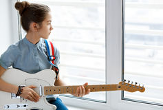 Beautiful young girl with guitar. Beautiful young girl with a guitar near the window Royalty Free Stock Images