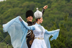 A beautiful young girl and a guy in a traditional Circassian costumes dance at the open Adyghe cheese festival in Adygea