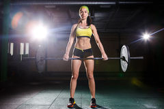 A beautiful young girl in the gym trains the muscles of the legs and back, deaet exercises deadlift, sits with weight, holds bar i. A beautiful young girl in the Royalty Free Stock Photo