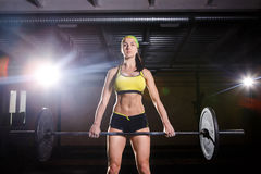 A beautiful young girl in the gym trains the muscles of the legs and back, deaet exercises deadlift, sits with weight, holds bar i. A beautiful young girl in the Royalty Free Stock Photos