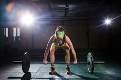 A beautiful young girl in the gym trains the muscles of the legs and back, deaet exercises deadlift, sits with weight, holds bar i. A beautiful young girl in the Stock Photos